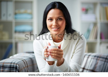 Happy girl in white pullover holding mug and looking at camera with smile - stock photo