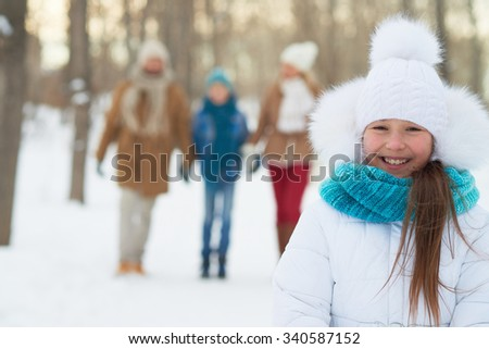 Happy girl in winterwear looking at camera with her parents and brother on background - stock photo