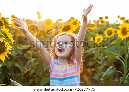 Happy girl is fond of sunflowers