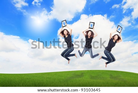 Happy Girl Jump and show touch pad computer (with WWW text) on the meadow with blue sky and white cloud, for cloud computing concept - stock photo