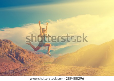 Happy girl jumping high in the mountains - stock photo