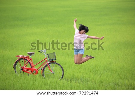 happy girl jumping in paddy field. - stock photo