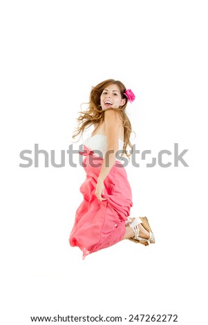 Happy girl jumping of joy in long pink dress with flower in hair smiling