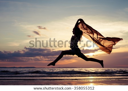 Happy girl jumping on the beach at the sunset time - stock photo
