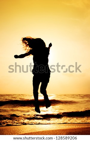 Happy girl jumping on the beach in sunset time - stock photo