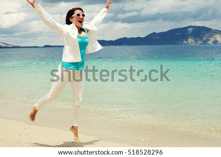 Happy girl jumping on the beach, summer holiday