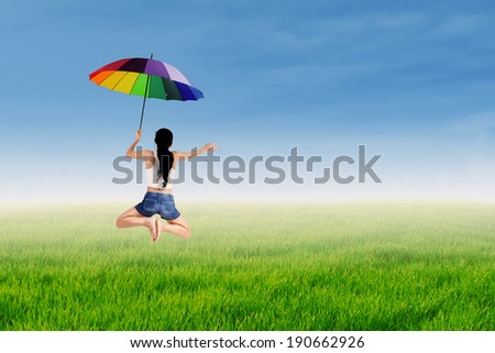 Happy girl jumping with a rainbow umbrella at green meadow
