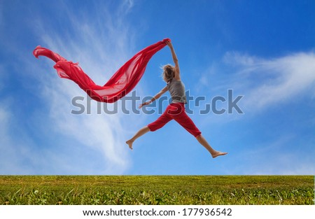 happy girl jumping with red fabric - stock photo