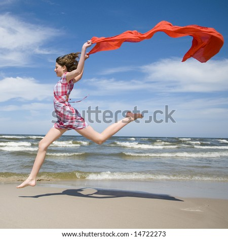 Happy girl jumping with scarf on the beach. - stock photo