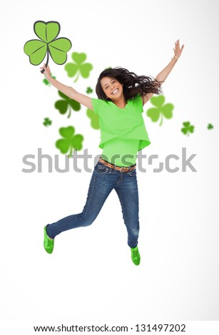 Happy girl jumping with shamrocks on white background