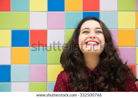 Happy girl laughing against a colorful tiles background. Concept of joy - stock photo