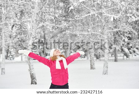 happy girl laughing, enjoying life and throws snow at winter outdoors - stock photo