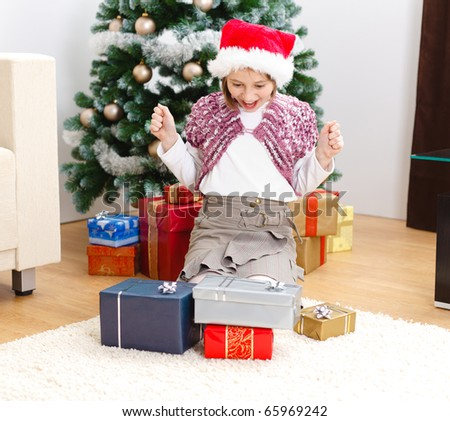 Happy girl looking at lots of presents in front of Christmas tree - stock photo