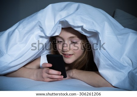 Happy Girl Looking At Mobile Phone While Lying Under Blanket On The Bed - stock photo