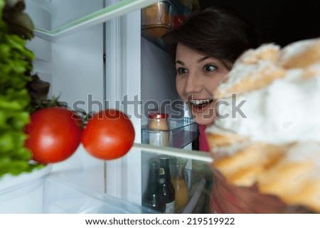 Happy girl looking into interior the fridge - stock photo