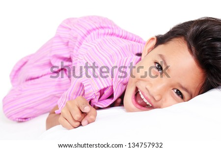 Happy girl lying on the bed ready for bedtime. - stock photo