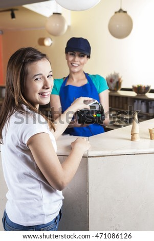 Happy Girl Making NFC Payment While Waitress Smiling
