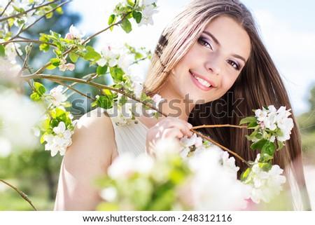 Happy girl near blossom cherry tree in spring garden - stock photo