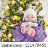 happy girl near the decorated christmas tree. looking at camera - stock photo