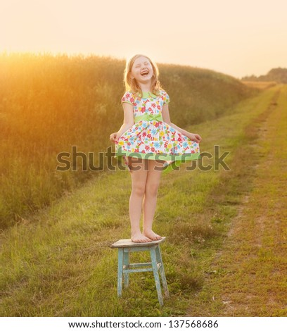 happy girl on chair outdoor - stock photo