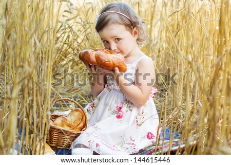 happy girl on field of wheat with bread - stock photo