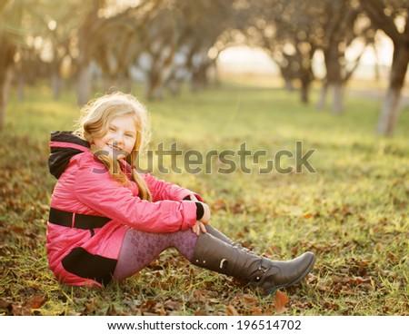 happy girl on grass in autumn garden - stock photo