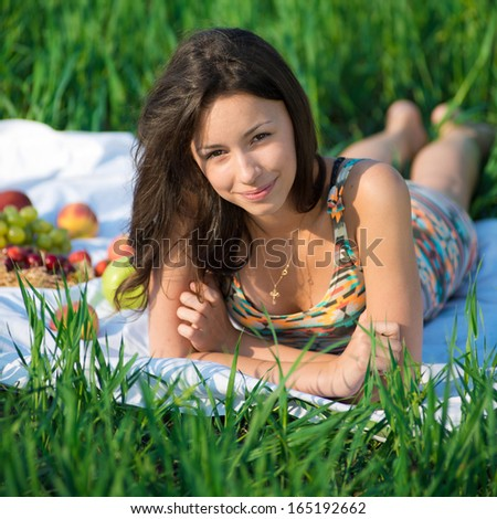 Happy girl on green grass at spring or summer park picnic