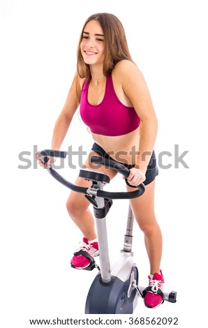 Happy girl on stationary bicycle - stock photo