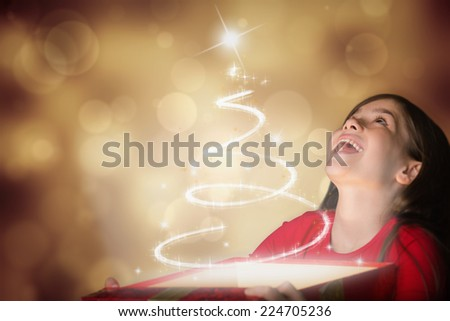 Happy girl opening gift box against orange abstract light spot design