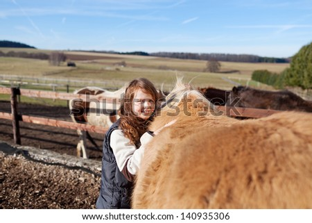 Happy girl petting her palomino horse in the back - stock photo