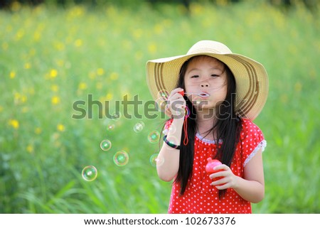 Happy girl play with soap bubbles on yellow flower field. - stock photo