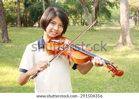 Happy girl playing her violin in the park. - stock photo