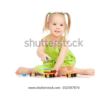 happy girl playing toy train on floor on white background - stock photo