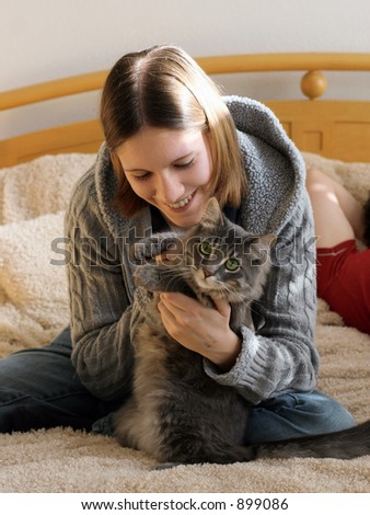 Happy girl playing with her kitten - stock photo