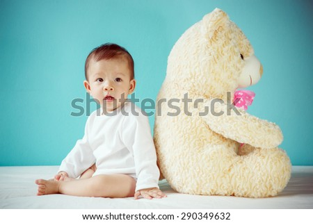 Happy girl playing with teddy bear - stock photo