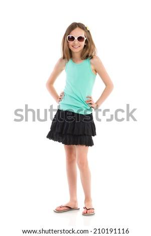 Happy girl posing in sunglasses. Little girl in teal shirt and black skirt posing in sunglasses. Full length studio shot isolated on white. - stock photo