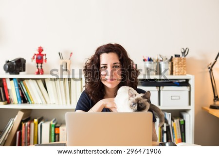 Happy girl posing with her cat in her home. - stock photo