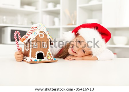 Happy girl preparing for christmas with gingerbread house - stock photo