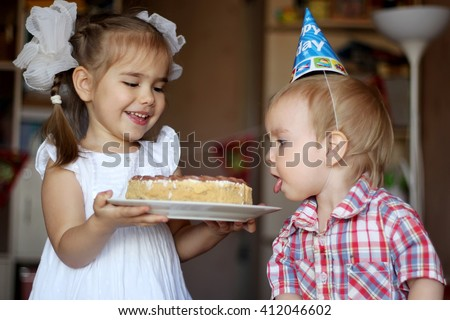 Happy girl proposing a cake to her little brother and he tasting it with the tongue, happy birthday concept - stock photo
