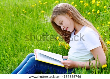 Happy girl reading book and sitting on green grass - stock photo