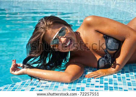 Happy girl relaxing in pool - stock photo
