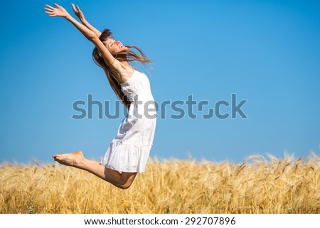 happy girl running jumping carefree with outstretched hands over yellow field and blue sky - stock photo
