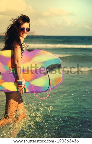 Happy girl running laughing cheerful having fun with boogieboard on summer holidays  - stock photo