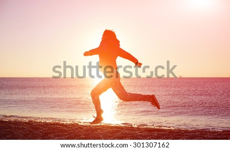 happy girl running on the beach at sunrise against the sun. silhouette