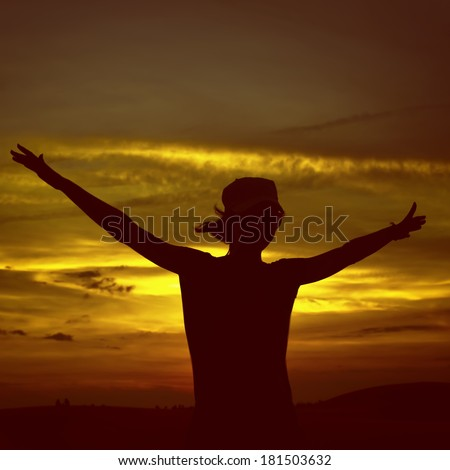Happy girl silhouette standing against sunset with arms raised up - stock photo