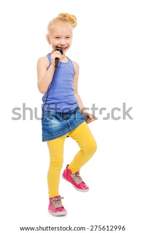 Happy girl singing in microphone and dancing - stock photo