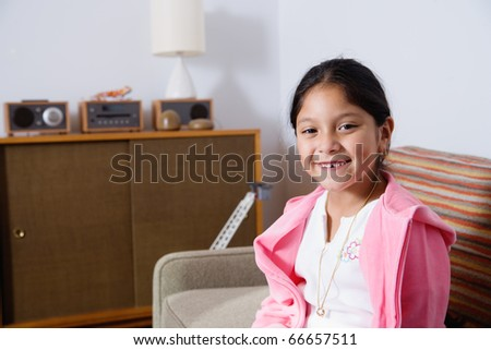 Happy girl sitting at home - stock photo