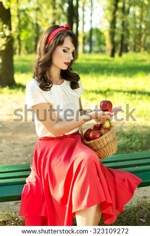 Happy girl sitting on a bench and holding a basket with apples. On nature - stock photo