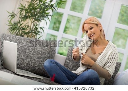 Happy girl sitting on the sofa and preparing her nails for a manicure - stock photo