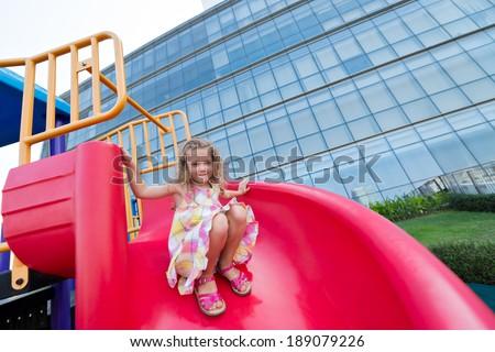Happy girl sliding on chute - stock photo
